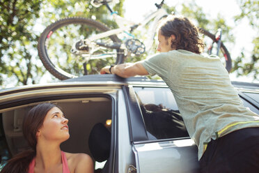 Woman looking at man standing by car with bicycle on roof - CAVF31254