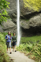Couple walking on footpath by waterfall in forest - CAVF31257