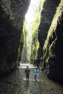 Couple walking in stream amidst rock formations - CAVF31260