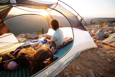 Couple relaxing in tent on mountain - CAVF31269
