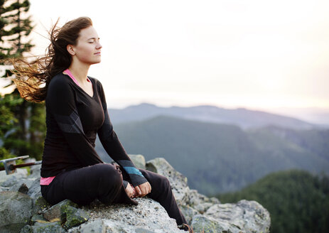 Woman meditating while sitting on rock formation against clear sky - CAVF31272