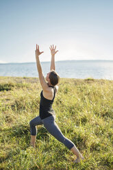 Woman practicing warrior pose on grassy field by sea against clear sky - CAVF31296
