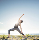 Woman practicing extended side angle pose yoga at beach during sunny day - CAVF31299