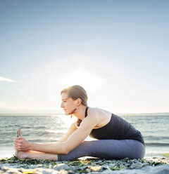 Woman practicing seated forward bend at beach against sky - CAVF31305