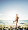 Woman meditating in tree pose at beach against sky - CAVF31308