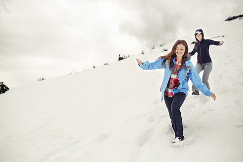 Cheerful female friends running on snow covered mountain against cloudscape - CAVF31314