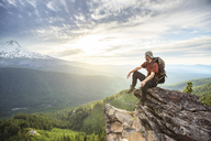 Hiker looking away while sitting on mountain against cloudy sky - CAVF31329
