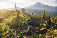 High angle view of hiker relaxing in hammock on mountain - CAVF31341