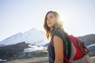 Woman with backpack looking away while standing against clear sky during sunny day - CAVF31344