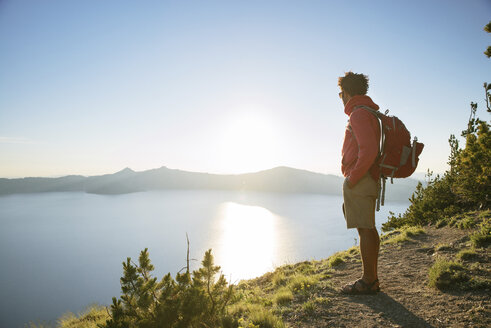 Hiker with backpack standing on mountain at Crater Lake National Park during sunny day - CAVF31362
