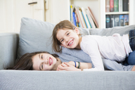 Portrait of two happy sisters cuddling on the couch - LVF06839