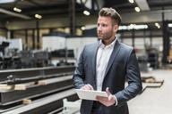 Businessman using tablet on factory shop floor - DIGF03553