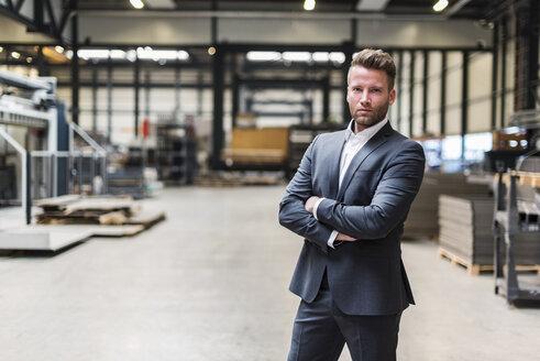 Portrait of confident businessman standing on factory shop floor - DIGF03556