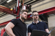 Two men with folder on factory shop floor looking around - DIGF03565