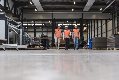 Three men wearing hard hats and safety vests walking on factory shop floor - DIGF03580
