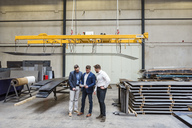 Three men standing on factory shop floor looking at tablet - DIGF03592