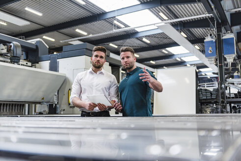 Two men with tablet discussing on factory shop floor - DIGF03607