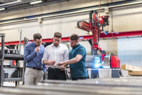 Three men sharing tablet on factory shop floor - DIGF03613