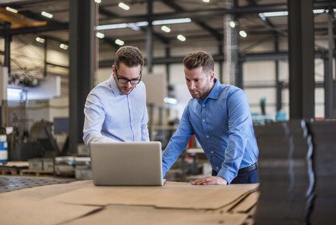 Two businessmen sharing laptop on factory shop floor - DIGF03616