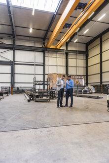 Two businessmen sharing tablet on factory shop floor - DIGF03625