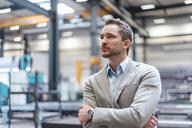 Portrait of businessman on factory shop floor thinking - DIGF03631