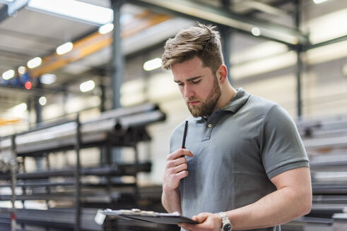 Man writing on clipboard on factory shop floor - DIGF03634