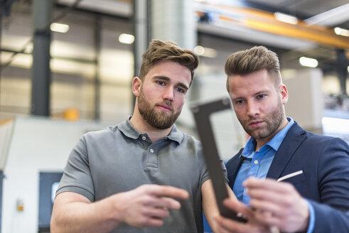 Employee and businessman examining workpiece on factory shop floor - DIGF03637