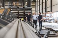 Three men talking on factory shop floor - DIGF03643