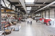 Three men walking and talking on factory shop floor - DIGF03646