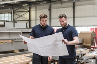 Two men looking at plan in factory - DIGF03649