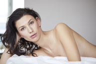 Portrait of attractive dark-haired young woman lying on bed - PNEF00561