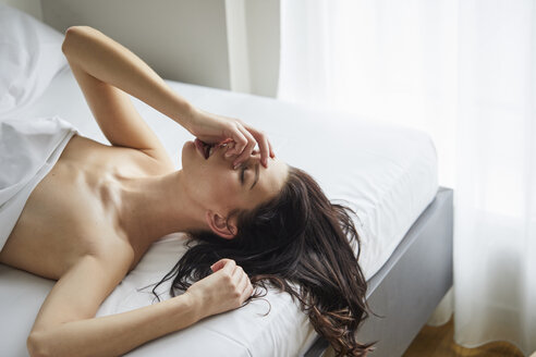 Seductive young woman lying on bed - PNEF00564