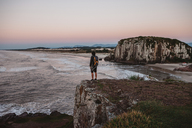 Rear view of male hiker standing on cliff at beach during sunset - CAVF31388