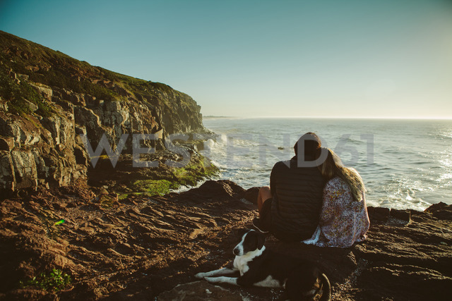 Couple and dog sitting on rock by sea against clear sky - CAVF31391