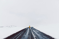 Mid distance of man standing on road amidst snow field against sky - CAVF31403
