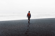 Rear view of woman walking on black sand beach against sky - CAVF31406