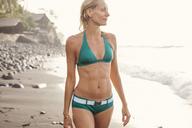 Thoughtful woman in bikini walking on beach during summer - CAVF31475
