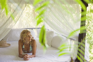 Thoughtful woman relaxing in gazebo - CAVF31484
