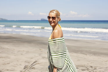 Side view portrait of happy woman on beach during summer vacation - CAVF31496
