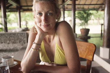 Portrait of beautiful woman sitting at restaurant in tourist resort - CAVF31502