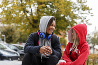 Girls in hoodies smiling at each other - FOLF05726