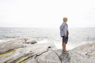 Boy standing on rocky seashore in the Stockholm archipelago - FOLF05735