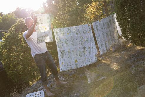 Mature man hanging sheet on laundry line - FOLF05741
