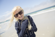 Smiling blonde girl wearing sunglasses on beach Carmel-by-the-Sea in Californa - FOLF05810