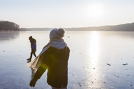 Germany, Brandenburg, Lake Straussee, two kids walking on frozen lake - OJF00252