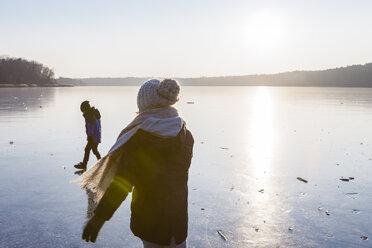 Germany, Brandenburg, Lake Straussee, two kids walking on frozen lake - OJF00252