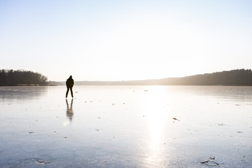 Germany, Brandenburg, Lake Straussee, frozen lake and silhouette of an ice skater - OJF00255
