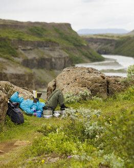 Tourist lying on edge of Hvita river canyon and reading - FOLF05861