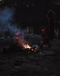 Men sitting by campfire at dusk - FOLF05918