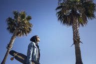 Low angle view of man holding skateboard amidst palm trees against clear blue sky - CAVF31597